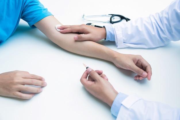 血液検査またはワクチンの注射後に粘着性の包帯の腕の静脈を置く医師