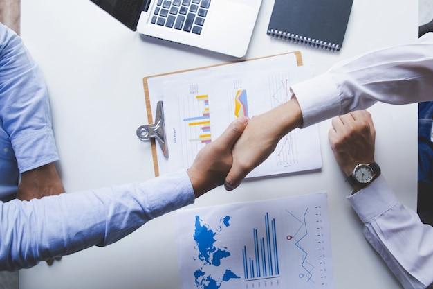 Вид сверху крупным планом деловые люди пожимают друг другу руки в офисе. завершение встречи
