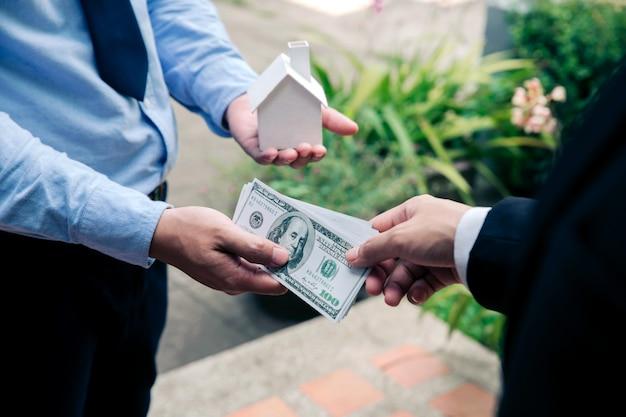不動産ローン、お金で実業家の手に家のモデルを与える手のクローズアップ。