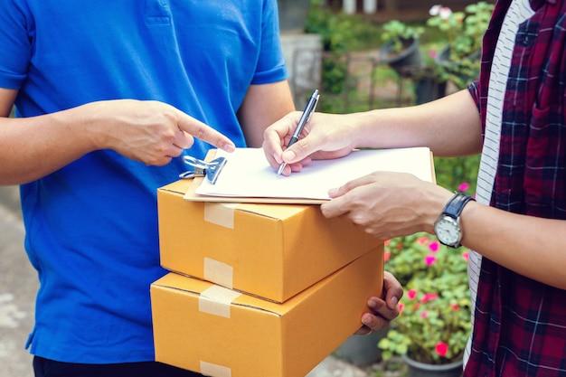 パッケージを取得するための署名。クリップボードに署名を入れて美しい若い男ながら段ボール箱を保持している若い配達人