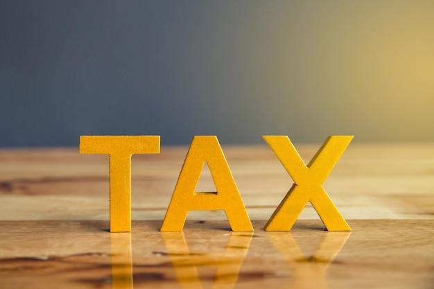 タックスの概念。木製の背景に置かれた税金