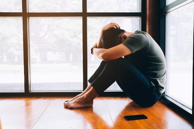 Подавленный человек грустный несчастный человек сидит на полу и держит лоб, имея головную боль