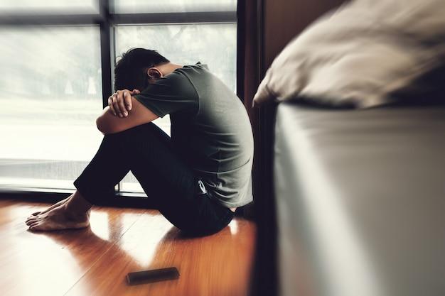 意気消沈した男。床に座って頭痛を抱えている間彼の額を保持している悲しい不幸な男