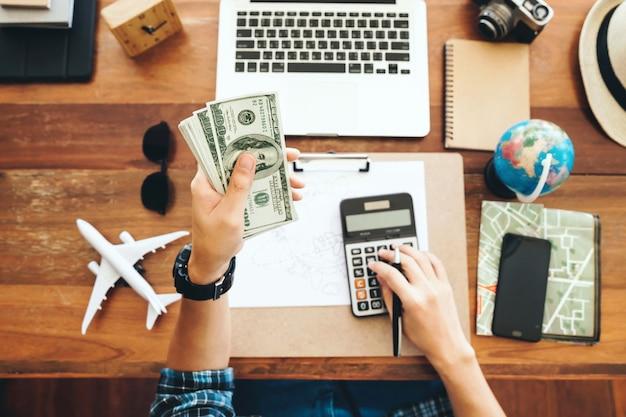 Вид сверху турист подсчитывает наличные деньги во время своего роскошного отпуска