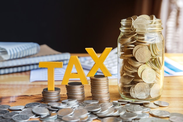 Налоговая концепция. валюта налога с уложенными монетами - калькулятор для ноутбука