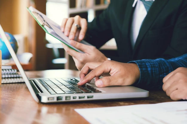 Рука бизнесмена держа диаграмму диаграммы и указывая диаграмму диаграммы для анализирует план продаж компании в офисе и рыночные данные партнера рассматривая на компьтер-книжках.