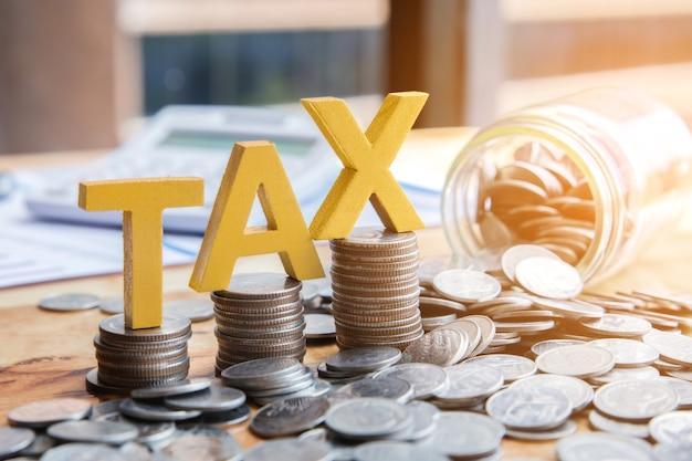 税コンセプト。積み重ねられた硬貨を持つ税金ノートブックの計算機があります