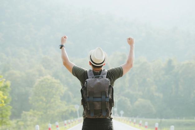 森で勝利の敬礼で空中で彼の手を上げるバックパックで幸せな観光客