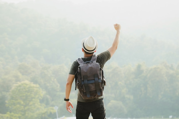Счастливый турист с рюкзаком поднимает руки в воздухе в победном салюте в лесу