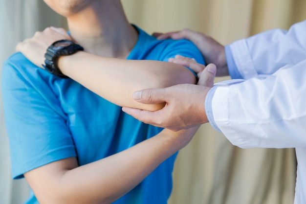 理学療法士と運動する肩の痛みと筋肉の男