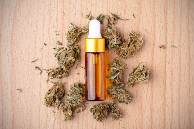 Эфирное масло из лекарственной конопли. марихуана на деревянном столе