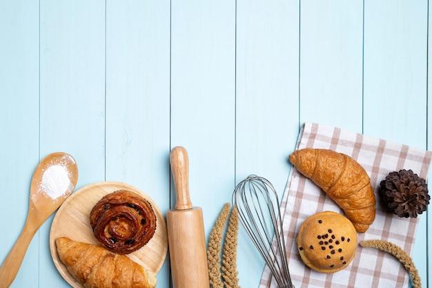 自家製のパンまたはパン、クロワッサン、麺棒、泡立て器、青い木の粉