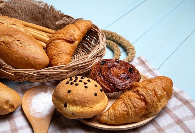 Хлеб пекарня на синий деревянный стол. различный хлеб и сноп колосьев пшеницы.