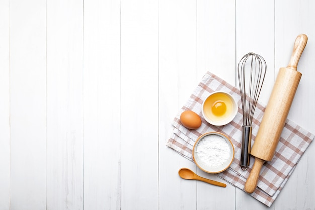 Пекарские ингредиенты. колосья пшеницы и миска муки, яйцо, скалка, венчик на белом
