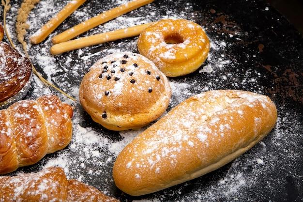 Различный покрытый коркой хлеб и плюшки на черной предпосылке доски.