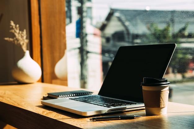 コーヒーマグカップ、テーブルの上にペンとラップトップ。
