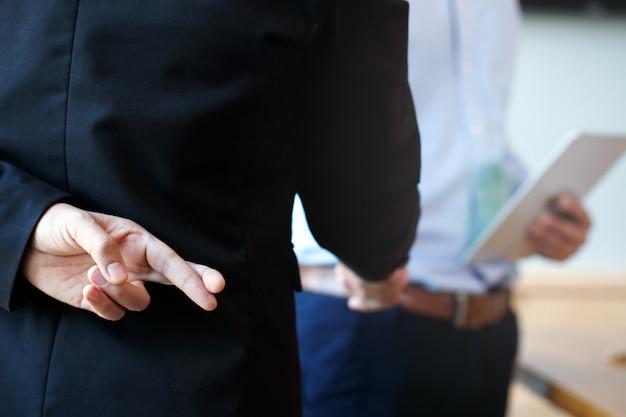 ビジネスパートナーが握手を交わしていますが。背中の後ろに交差指を保持しているビジネスの男性