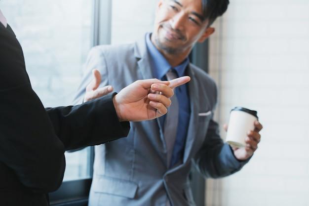 Бизнесмены изучают документы, разговаривают и улыбаются, стоя в офисе