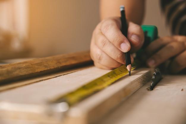 Плотник в мастерской отмечает на деревянной доске в мастерской