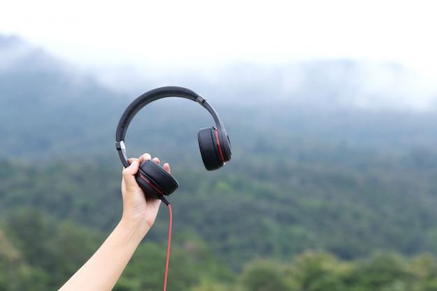 自然の背景を持つヘッドフォンを持っている手を閉じる