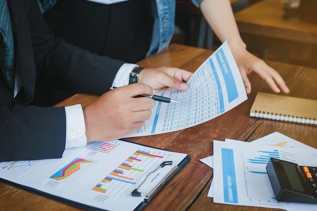 Бизнесмены комментируя и показывая график роста и принимая деловую беседу в офисе. обсуждает рост компании