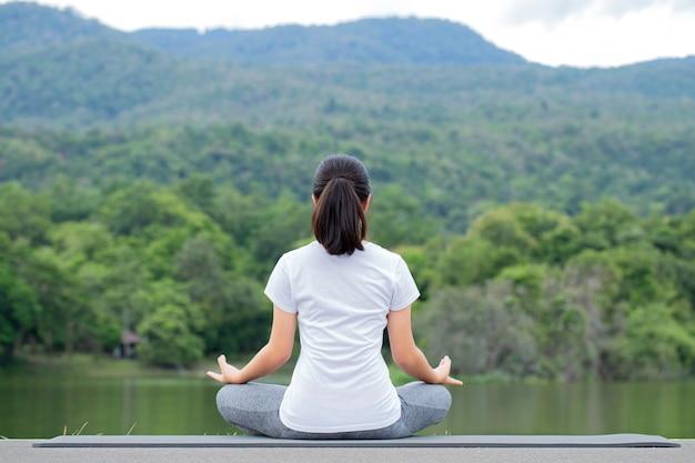 自然の中でヨガの練習の若い女性。瞑想。