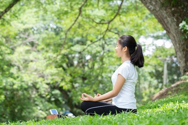 ヨガの練習と自然の中で音楽を聴く若い女性。アジアの女性は都市公園でヨガを練習しています。