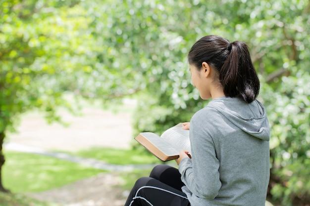 公園で聖書を読んでかなり若い女性。本を読んでいる。神の聖書の概念は信仰と霊性に基づいています。