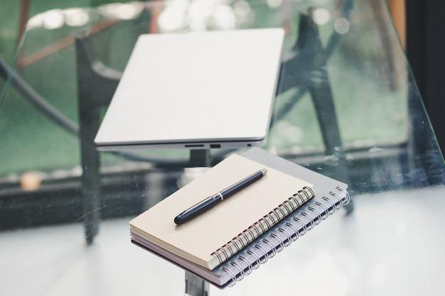 Блокноты и ноутбук размещены на журнальном столике.