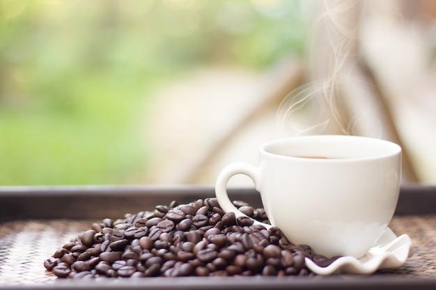 白いコーヒーのマグカップとコーヒー豆は、背景をぼかし、ホットコーヒーのカップは、コーヒー豆の横に配置されます。