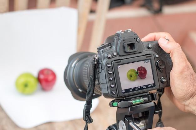 カメラマンは、白い背景の上の果物を撮影するデジタル一眼レフカメラを使用しています