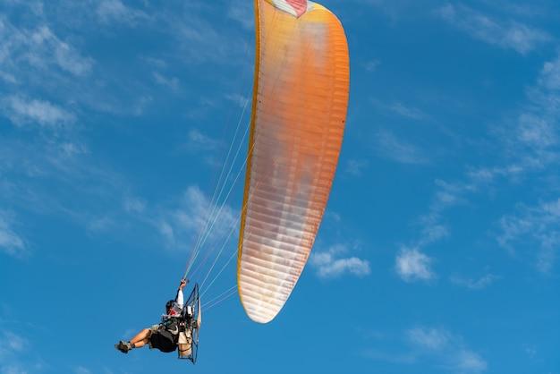 Люди играли в парамотор, летая на голубом небе. красивый фон природы.