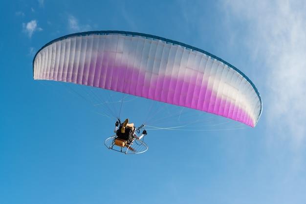 Люди играли парамотор, летящий на фоне голубого неба