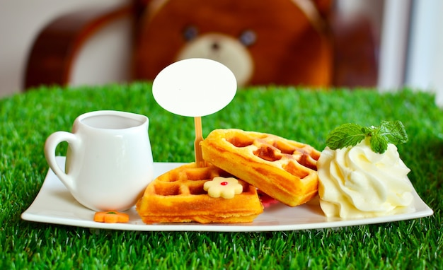 白い皿と緑の草の上に白い蜂蜜のワッフルとホイップクリーム