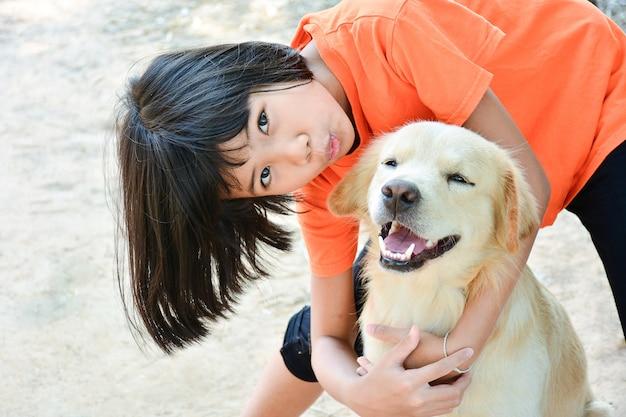 小さな子供のアジアの女の子は、彼女の犬を抱きしめる