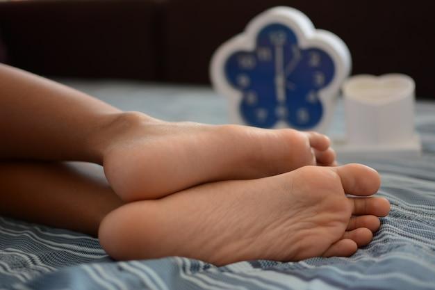 小さな女の子はぼんやりとした目覚まし時計で寝る