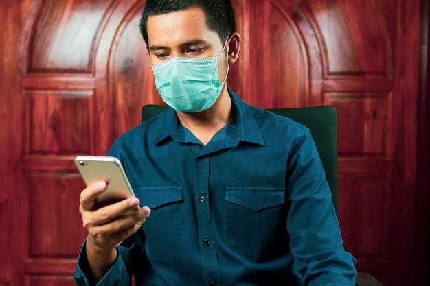 ストレスのたまったアジア人男性がコロナウイルスを防ぐためにフェイスマスクをつけた椅子に座る