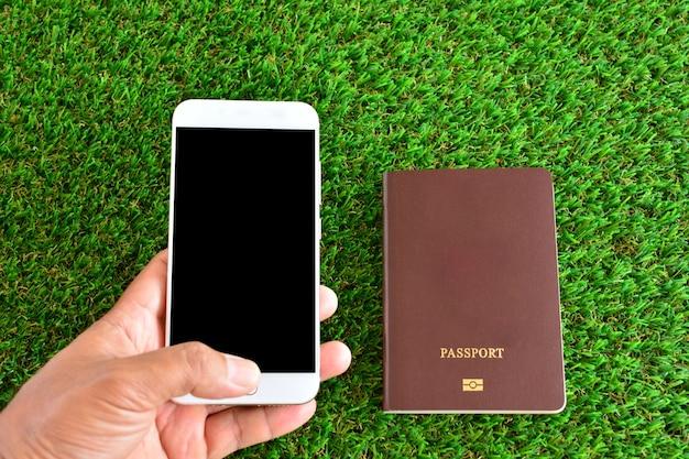 手を携帯電話を持って、緑の草の上にポートを渡します。ビジネスや旅行に使用できます