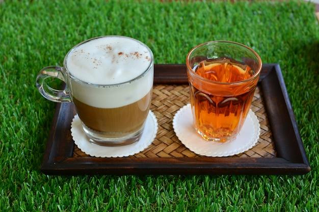 籐の皿と緑の草の上にホットコーヒーとホットティー。新鮮な朝のコンセプト。
