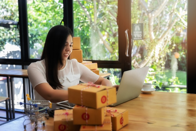 オンライン販売と彼女のホームオフィスで小包の出荷を持つ女性実業家。