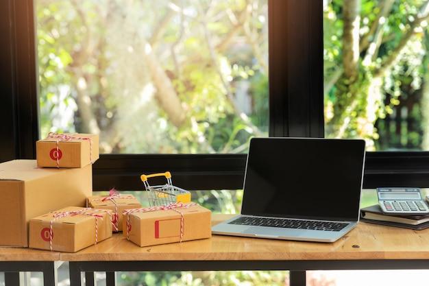 段ボールの小包箱とオンライン販売のための職場で机の上のノートパソコン。