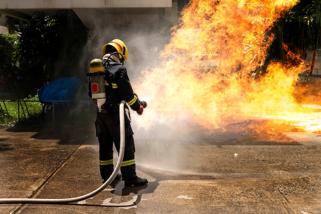 緊急事態において消防士は火炎を消火します。