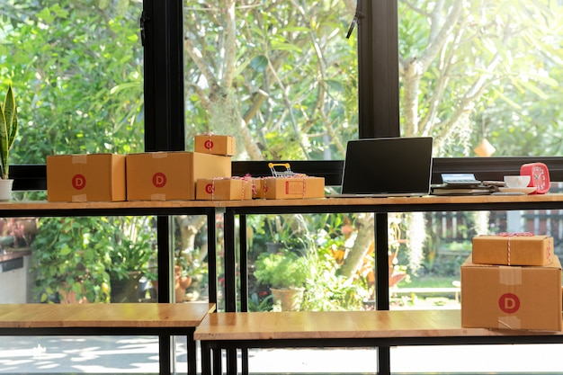 段ボールの小包箱と机の上のノートパソコン。