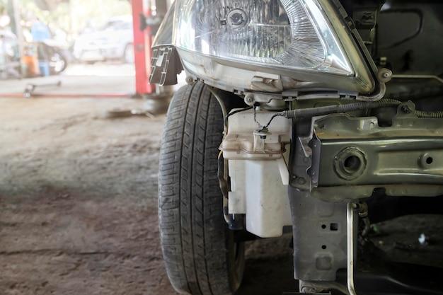車の修理ガレージで修理されるのを待っている損傷した車のクローズアップ