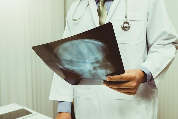 Врач диагностирует и анализирует рентгеновский снимок пациента.