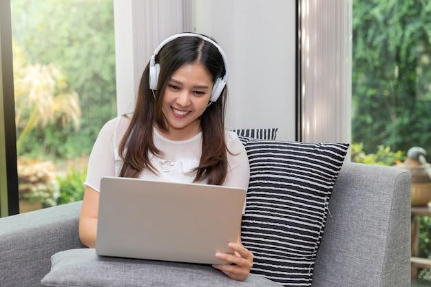 女性はソファーに座っているとタブレットを使用してヘッドフォンを着用します。