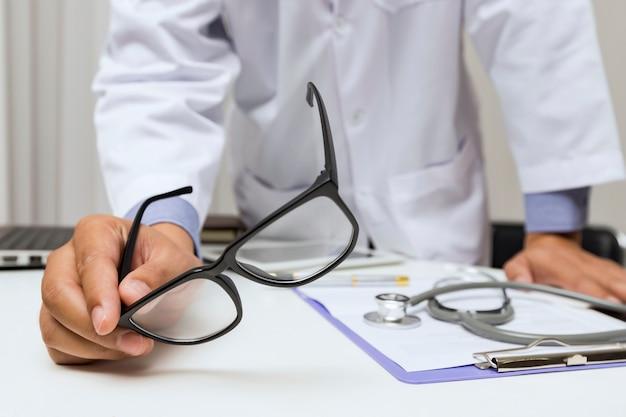 Доктор, держа его очки во время разговора с его пациентом.
