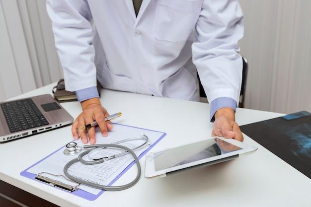 Доктор работает с планшетного компьютера на столе.
