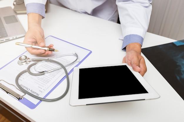 Доктор работая с планшетом на столе.