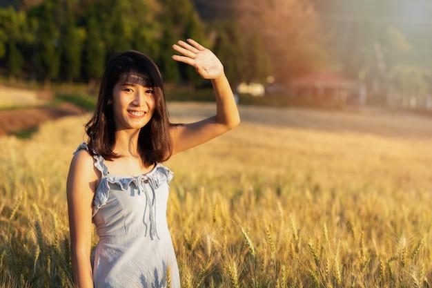 Красивая и счастливая азиатская женщина наслаждаясь жизнью в поле ячменя на заходе солнца